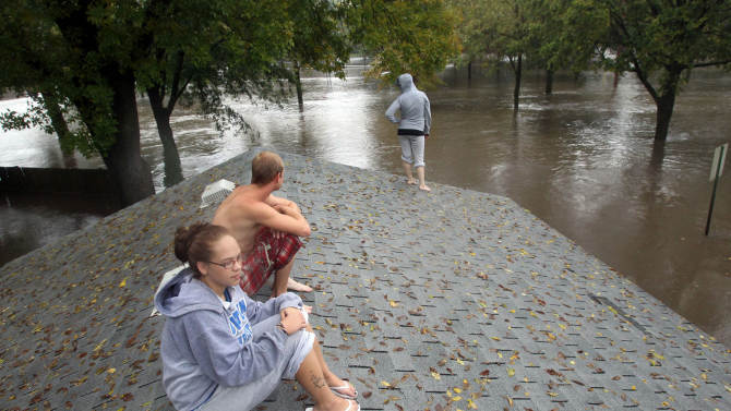 FILE - In this Sept. 23, 2010 file photo, Carrie Larson, front, watches from her family's garage roof with friends as floodwaters rise around her house in Owatonna, south of St. Paul, Minn.  The National Weather Service says conditions are ripe in 2011 for moderate to severe flooding along the upper Mississippi River from its headwaters near St. Paul, which has a 95 percent chance of flooding, to St. Louis. (AP Photo/Star Tribune, David Joles, File) MANDATORY CREDIT; ST. PAUL PIONEER PRESS OUT; MAGS OUT; TWIN CITIES TV OUT.