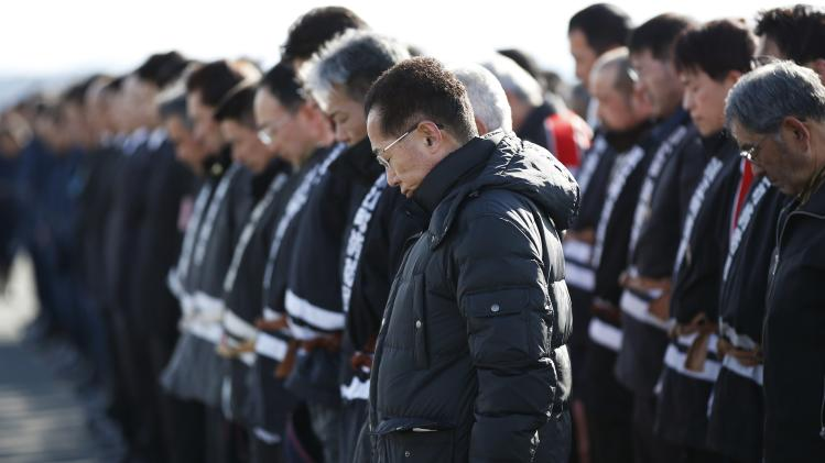 Police officers and firefighters observe a moment of silence at 2:46 p.m. (0546 GMT), the time when the magnitude 9.0 earthquake struck off Japan's coast in 2011, in Namie town