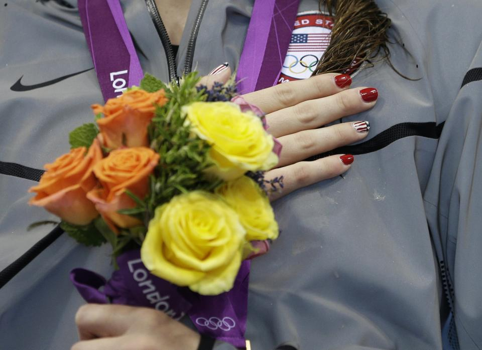 United States' Missy Franklin listens to the national anthem after receiving her gold medal for the women's 100-meter backstroke swimming final at the Aquatics Centre in the Olympic Park during the 2012 Summer Olympics in London, Monday, July 30, 2012. (AP Photo/Michael Sohn)
