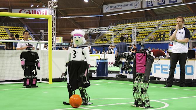 In this photo taken Thursday, June 27, 2013, a robot from the University of Bonn dribbles around a Japanese competitor at the RoboCup championships in Eindhoven, Netherlands. Around 300 teams from 40 countries are competing this week at the RoboCup. The competition has the long-term goal of building a team of androids good enough to beat the human world cup team by 2050. (AP Photo/Toby Sterling)
