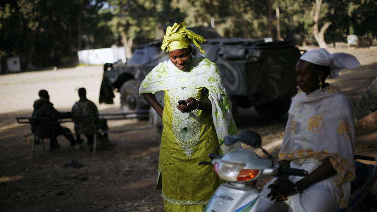 A Malian woman checks her phone in front of Malian soldiers in Niono, some  400 kms (300 miles) North of the capital Bamako Saturday Jan. 19, 2013. French troops encircled a key Malian town on Friday, trying to stop radical Islamists from striking against communities closer to the capital and cutting off their supply line, a French official said. The move around Diabaly came as French and Malian authorities said that the city whose capture prompted the French military intervention in the first place was no longer in the hands of the extremists.(AP Photo/Jerome Delay)