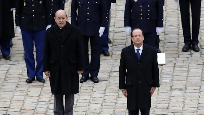 France's President Francois Hollande, left, and Defense Minister Jean-Yves Le Drian listen to national anthems during a military medals ceremony at Invalides in Paris, Tuesday Nov. 26, 2013. France will send 1,000 troops to Central African Republic under an expected U.N.-backed mission to keep growing chaos at bay, the defense minister said Tuesday boosting the French military presence in Africa for the second time this year.. (AP Photo/Francois Mori)