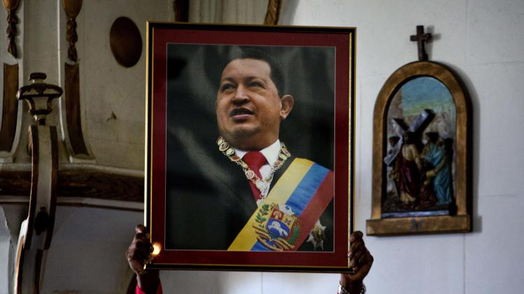 "A Venezuelan embassy worker holds up a framed image of Venezuela's ailing President Hugo Chavez during the monthly Catholic service devoted to the sick at the Church of Our Lady of Regla, in Regla, across the bay from Havana, Cuba, Tuesday, Jan. 8, 2013. Venezuela's government said Monday, Chavez is in a ""stable situation"" in a Cuban hospital receiving treatment due to a severe respiratory infection. The update came as other government officials reiterated their stance that the president need not be sworn in for a new term as scheduled this Thursday and could instead have his inauguration at a later date. (AP Photo/Ramon Espinosa)"