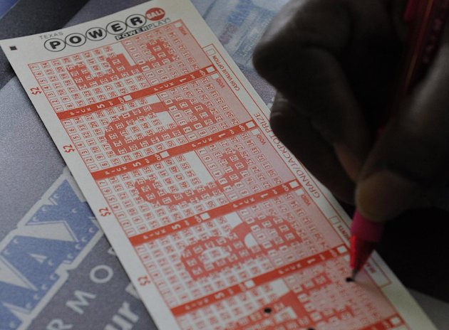A customer fills in his numbers on a Powerball ticket for a chance to win the $450,000 jackpot Monday, Nov. 26, 2012, in Houston for a chance to win the $450,000 jackpot. (AP Photo/Pat Sullivan)