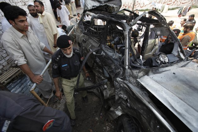 A policeman and residents gather near a damaged car at the site of a bomb blast in Peshawar