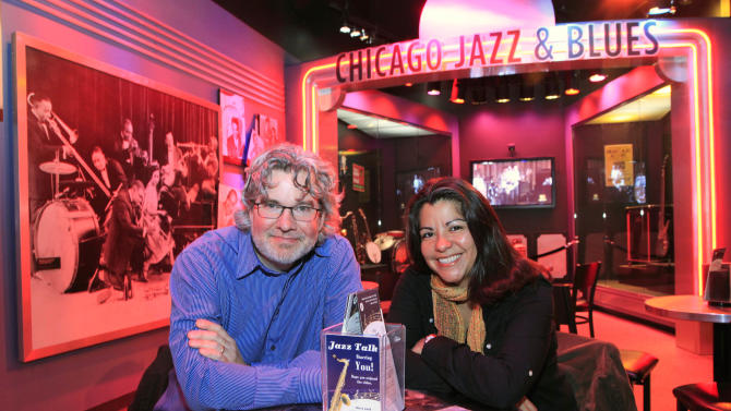 """In this photo taken Monday, Oct. 24, 2011, Kelly Leonard, left, vice-president at the Second City comedy club and Liz Garibay with the Chicago History Museum, sit within a display highlighting Chicago's Jazz and Blues history at the museum in Chicago. Second City, famed for its parody and improvisation, has partnered with the museum to turns its wit on Chicago itself. The finished product, """"Second City's History of Chicago,"""" previewing in late November, will likely touch on familiar subjects like the historical cast of political characters,the miserably cold winters, and the woebegone Chicago Cubs. (AP Photo/Charles Rex Arbogast)"""