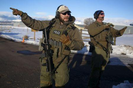 FBI agents  talk as they man the entry to the Burns Municipal Airport in Burns, Oregon