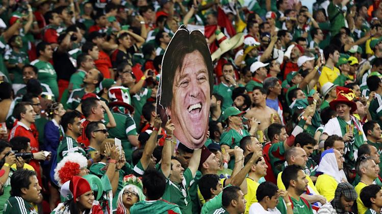 Mexico's fans celebrate holding a mask of Mexico's head coach Miguel Herrera after  the group A World Cup soccer match between Croatia and Mexico at the Arena Pernambuco in Recife, Brazil, Monday, June 23, 2014. Mexico won 3-1