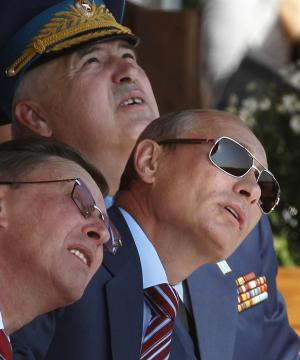 Russian Prime Minister Vladimir Putin, right, First Vice Premier Sergei Ivanov, left, and Col.-Gen. Alexander Zelin, center, attend the MAKS-2011 International Aviation and Space Show in Zhukovsky, outside Moscow, Russia, Wednesday, Aug. 17, 2011. (AP Photo/Mikhail Metzel)