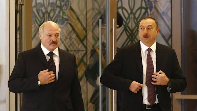 Belarus' President Lukashenko and his Azerbaijani counterpart Aliyev walk during their meeting in Minsk