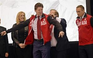 Canada's Men's Olympic Ice Hockey Team head coach Mike Babcock dons a team jacket during a news conference in Toronto