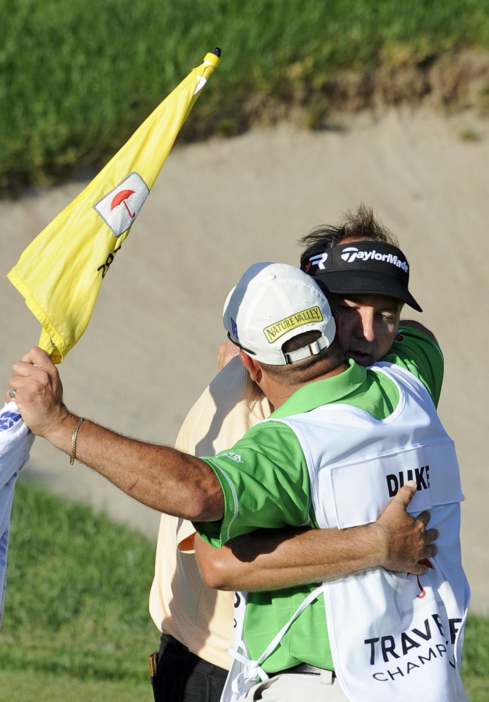 Ken Duke celebrates, right, with his caddie after winning the Travelers Championship golf tournament in Cromwell, Conn., Sunday, June 23, 2013. Duke won the second playoff hole against Chris Stroud. (AP Photo/Fred Beckham)