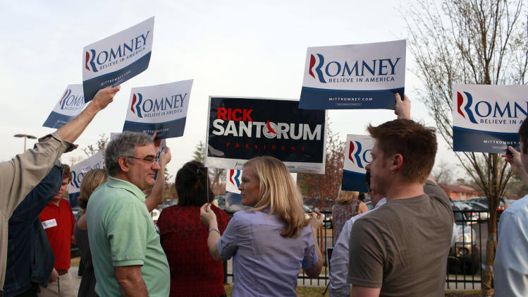 Libby Wilkinson holds a sign for Republican presidential candidate and former Pennsylvania Sen. Rick Santorum as supporters for Mitt Romeny hold signs for their candidate outside an event for Santorum at Westminster Christian Academy Saturday, March 17, 2012, in Town and Country, Mo. (AP Photo/Jeff Roberson)