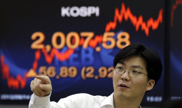 A currency trader reacts near a screen showing the Korea Composite Stock Price Index (KOSPI) at the foreign exchange dealing room of the Korea Exchange Bank headquarters in Seoul, South Korea, Friday, Sept. 14, 2012. Asian stock markets bound higher Friday after investors got just what they wanted - big moves by the Federal Reserve to help the U.S. economy out of its funk. (AP Photo/Lee Jin-man)
