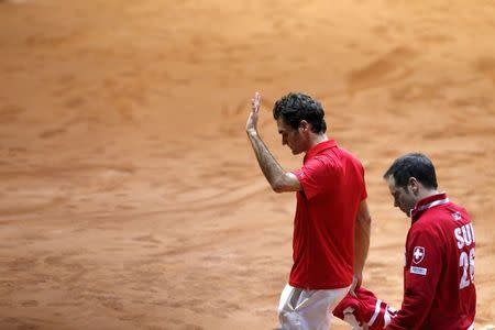 Switzerland's Roger Federer and team captain Severin Luthi leave after their Davis Cup final singles tennis match against France's Gael Montfils at the Pierre-Mauroy stadium in Villeneuve d'Ascq