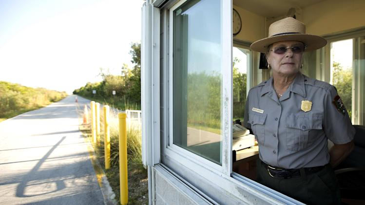 Park Ranger Christine MacKarvich mans the Shark Valley entrance booth in Everglades National Park, early Tuesday, Oct. 1, 2013. She was told to report to work but had been warned that a call from the park service would shut the park down. The partial government shutdown that began Tuesday left many federal workers uncertain of their financial future, with many facing unpaid furloughs or delays in paychecks. A midnight deadline to avert the shutdown passed amid congressional bickering, leaving Americans unable to get government services ranging from federally backed home loans to supplemental food assistance for children and pregnant women.(AP Photo/J Pat Carter)