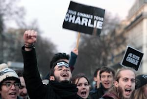 """People shout slogans while holding a sign reading """"Nous…"""