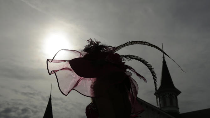 Karen Vanzant, from Brookfield, Colo., walks through the paddock with her fancy hat before the running of the 139th Kentucky Oaks at Churchill Downs Friday, May 3, 2013, in Louisville, Ky. (AP Photo/Charlie Riedel)