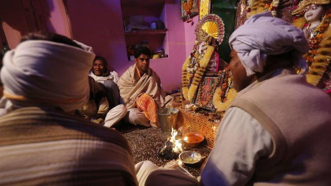 Hindu priest Hiralal prays inside temple before jumping out of fire to signify burning of demon Holika during ritual to mark first day of Holi at village Phalen