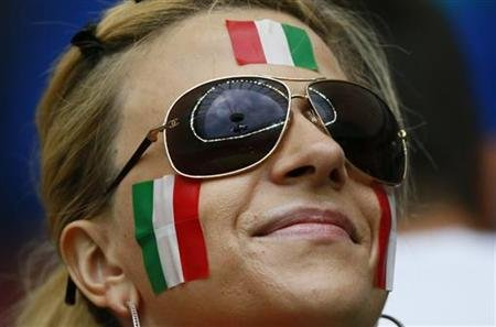 The top of the National Stadium is reflected in sunglasses of a fan of Italy before the start of the Euro 2012 semi-final soccer match between Italy and Germany in Warsaw