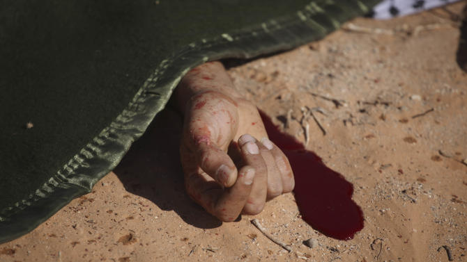 A former rebel fighter lays shrouded after a rocket propelled grenade accident in Wadi Dinar, Libya, Wednesday, Sept. 21, 2011.  A commander of new government's forces said late Tuesday they were in control of most of the Gadhafi desert stronghold of Sabha after a day of fighting. The commander, Bashir Ahwaz, said most of the tribesmen loyal to Gadhafi fled the city instead of putting up a fight. (AP Photo/Alexandre Meneghini)