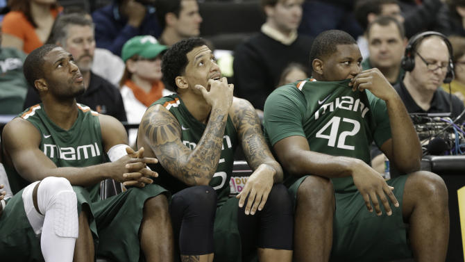 Miami players, from left, Raphael Akpejiori, Julian Gamble, and Reggie Johnson, look on during the second half of an NCAA college basketball game against Wake Forest in Winston-Salem, N.C., Saturday, Feb. 23, 2013. Wake Forest won 80-65. (AP Photo/Chuck Burton)