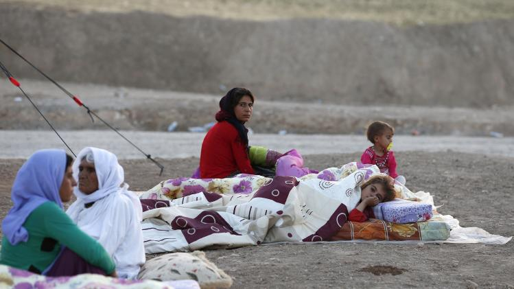 Displaced people from the minority Yazidi sect rest among their bedding, placed on the open ground, at Bajed Kadal refugee camp, southwest of Dohuk province
