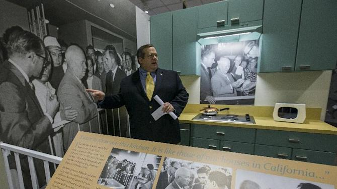 In this Tuesday, Feb. 12, 2013 photo, curator Bob Bostock, a former Richard Nixon aide who designed the original Watergate exhibit, points at the famous Soviet Premier Nikita Khrushchev picture, inside a re-creation of the 1950s-era modern American kitchen exhibited in Moscow where Nixon and Khrushchev had their fiery exchange debating the merits of freedom versus communism, on display at the Richard Nixon Presidential Library and Museum in Yorba Linda, Calif. (AP Photo/Damian Dovarganes)