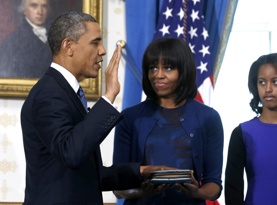 President Barack Obama is officially sworn-in by Chief Justice John Roberts, not pictured, in the Blue Room of the White House during the 57th Presidential Inauguration in Washington, Sunday, Jan. 20, 2013, as first lady Michelle Obama, holds the Robinson Family Bible, and daughter Malia watches. (AP Photo/Larry Downing, Pool)