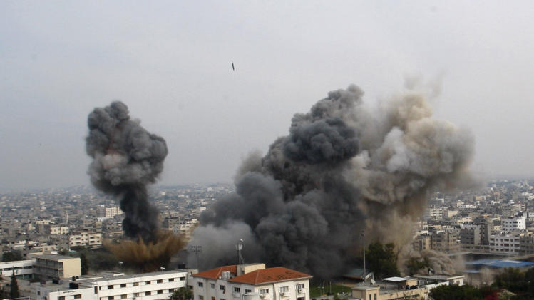 Smoke raises as another missile approaches the target during an Israeli air strike in Gaza City, Wednesday, Nov. 21, 2012. Israeli aircraft pounded Gaza with at least 30 strikes overnight, hitting government ministries, smuggling tunnels, a banker's empty villa and a Hamas-linked media office.  (AP Photo/Hatem Moussa)