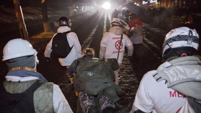 Medics transport an injured protester during an attack of the Ukrainian House building in central Kiev, Ukraine, early Sunday, Jan. 26, 2014. New violence erupted in Ukraine's capital during the night as a large crowd attacked the government exposition and conference hall where police were stationed inside. Early Sunday, demonstrators were throwing firebombs into the Ukrainian House building and setting off fireworks, and police responded with tear gas. (AP Photo/Evgeny Feldman, Novaya Gazeta)