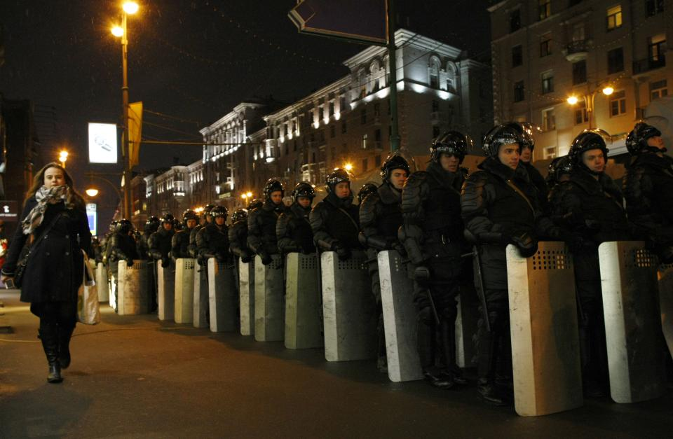 A woman walks past a line of riot police officers near the site of protest in downtown Moscow, Monday, March 5, 2012. A large rally held Monday was sanctioned by authorities but security was tight, with some 12,000 police deployed to ensure order. (AP Photo/Alexander Zemlianichenko)