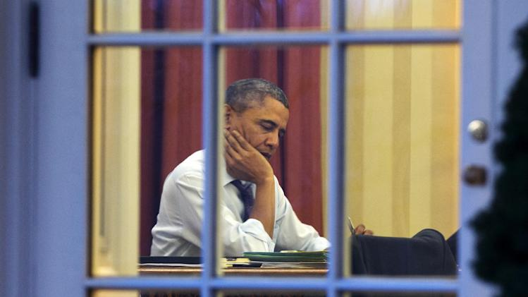 President Barack Obama works at his desk in the Oval Office of the White House in Washington, Monday, Jan. 27, 2014, ahead of Tuesday night's State of the Union speech. (AP Photo/Jacquelyn Martin)