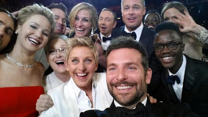 "This image released by Ellen DeGeneres shows actors front row from left, Jared Leto, Jennifer Lawrence, Meryl Streep, Ellen DeGeneres, Bradley Cooper, Peter Nyong'o Jr., and, second row, from left, Channing Tatum, Julia Roberts, Kevin Spacey, Brad Pitt, Lupita Nyong'o and Angelina Jolie as they pose for a ""selfie"" portrait on a cell phone during the Oscars at the Dolby Theatre on Sunday, March 2, 2014, in Los Angeles. (AP Photo/Ellen DeGeneres)"