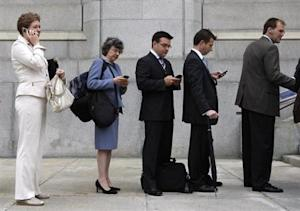 People use mobile devices while waiting to enter the Supreme Court of Canada in Ottawa