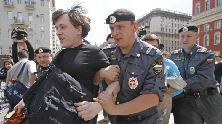 Russian police officers detain a gay rights activist during an attempt to hold a gay pride parade in Moscow, Russia, Sunday, May 27, 2012. Russian police have detained around a dozen protesters demanding the right to hold a gay pride parade in Moscow. Activists have long petitioned the Moscow government for permission to stage such a parade, but have always been denied. (AP Photo/Mikhail Metzel)