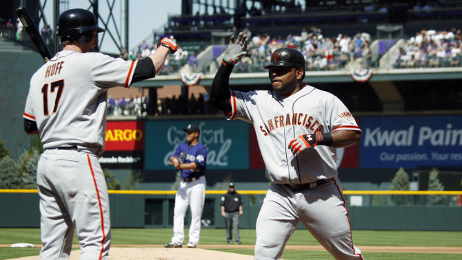 San Francisco Giants on-deck batter Aubrey Huff, left, congratulates Pablo Sandoval as Sandoval returns to the dugout after hitting a two-run home run against the Colorado Rockies in the first inning of a baseball game in Denver on Monday, April 9, 2012. (AP Photo/David Zalubowski)