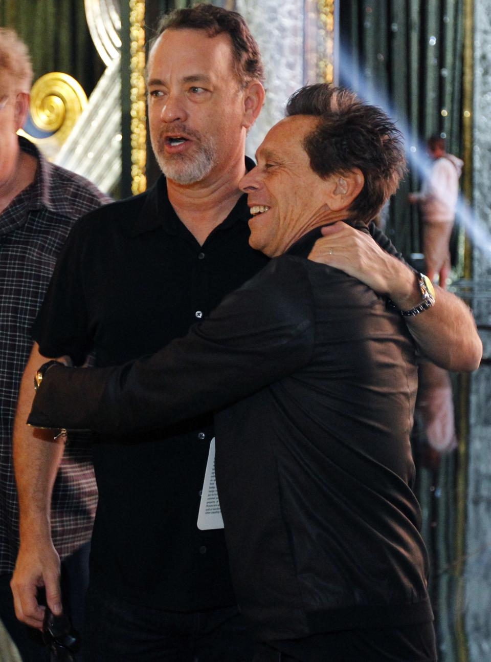 Actor Tom Hanks, left, and Brian Grazer, producer of the 84th Academy Awards, embrace during rehearsals for Sunday's show Saturday, Feb 25, 2012 in Los Angeles. (AP Photo/Chris Carlson)