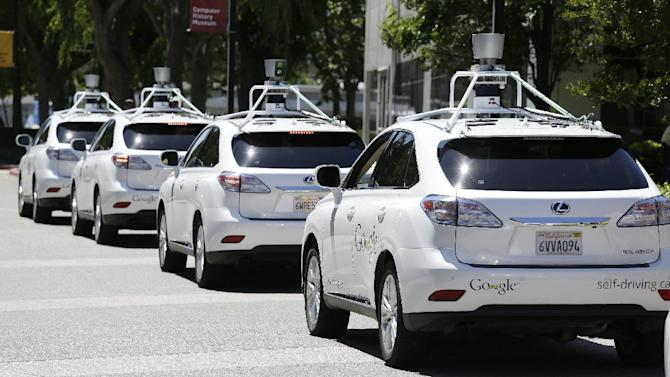 """FILE - This file photo taken Tuesday, May 13, 2014 shows a row of Google self-driving cars outside the Computer History Museum in Mountain View, Calif. California's Department of Motor Vehicles will miss a year-end deadline to adopt new rules for cars of the future because regulators first have to figure out how they'll know whether """"driverless"""" vehicles are safe. (AP Photo/Eric Risberg,File)"""