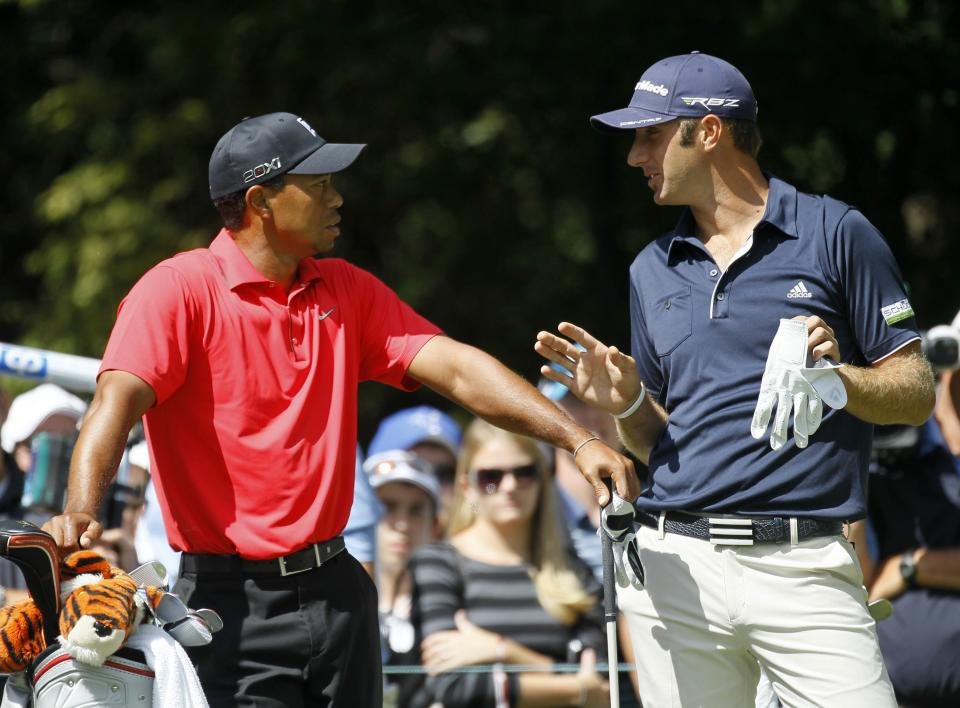 Tiger Woods, left, listens to Dustin Johnson at the tee box of the second hole during the final round of the BMW Championship PGA golf tournament at Crooked Stick Golf Club in Carmel, Ind., Sunday, Sept. 9, 2012. (AP Photo/Charles Rex Arbogast)