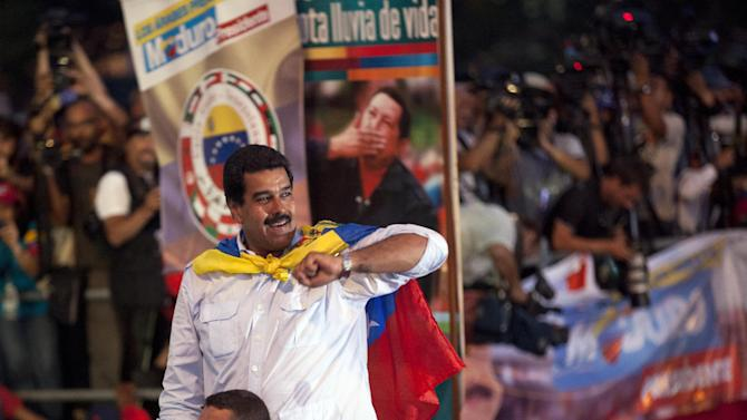 Venezuela's acting President Nicolas Maduro greets supporters as he arrives to Bolivar Ave. for his closing campaign rally in Caracas, Venezuela, Thursday, April 11, 2013. Maduro, the hand-picked successor of Venezuela's late President Hugo Chavez, is running for president against opposition candidate Henrique Capriles on April 14. (AP Photo/Ramon Espinosa)