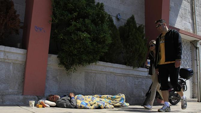 Pedestrians walk by a homeless man in Thessaloniki, Greece, Sunday, April 21. 2013. Under an international bailout deal that saved it from bankruptcy in 2010, Greece agreed to slash bloated budget deficits, repeatedly cutting pensions and salaries while hiking taxes. (AP Photo/Nikolas Giakoumidis)