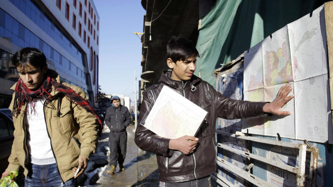 In this Wednesday, Feb. 6, 2013 photo, Afghan actor Fawad Mohammadi 14, adjusts a pasted map displaced to sell on Chicken St., the main tourist area in Kabul, Afghanistan. Fawad Mohammadi has spent half his life peddling maps and dictionaries to foreigners in the main tourist district in Kabul. Now the 14-year-old Afghan boy with beautiful green eyes is getting ready for his first airplane ride and a trip down the red carpet at the Oscars. (AP Photo/Musadeq Sadeq)