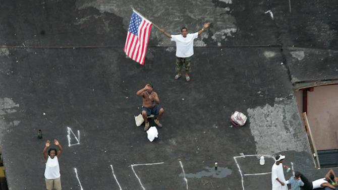FILE - In this Sept. 1, 2005, file photo, residents wait on a rooftop to be rescued from the floodwaters of Hurricane Katrina in New Orleans. Dozens of lawsuits seeking damages from the federal government for Hurricane Katrina-related levee failures and flooding in the New Orleans area are over. U.S. District Judge Stanwood Duval Jr. has dismissed the cases. The move comes more than a year after a federal appeals court overturned his ruling that held the U.S. Army Corps of Engineers liable for flooding caused by lax maintenance of a shipping channel. (AP Photo/David J. Phillip, Pool, File)