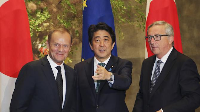 European Council President Donald Tusk, European Commission President Jean-Claude Juncker and Japan's Prime Minister Shinzo Abe wait for the arrival of Abe's cabinet members for a group photo session before their meeting