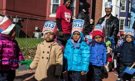 School children walk past a polling station in Washington, D.C. on Nov. 6.: The high school graduation rate in America is just above 75 percent, which is well below that of many other first-world nations.