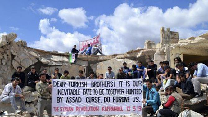 In this Sunday, May 12, 2013 citizen journalism image provided by Union of Homs Districts which has been authenticated based on its contents and other AP reporting, shows anti-Syrian regime protesters holding a banner in the remains of a building, during a demonstration at Kafr Nabil, in Idlib province, northern Syria. Syrian troops have reportedly taken full control of a town near the highway linking the capital Damascus with Jordan, a new advance in the regime's campaign to drive rebels from the strategic south, an activist group said Monday. (AP Photo/Union of Homs Districts)