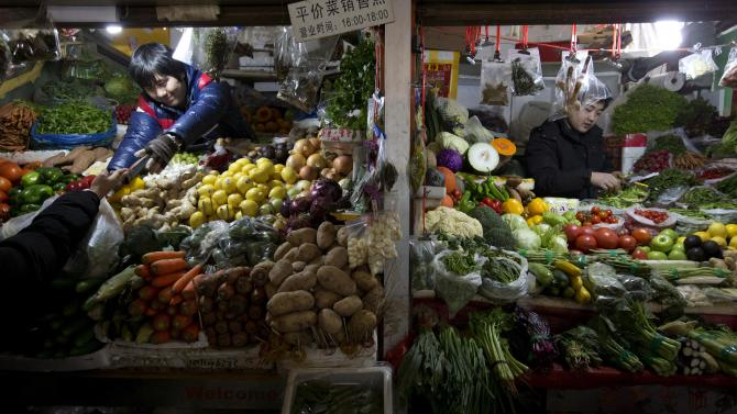 A vegetable vendor, left, collects money from a customer at a market in Beijing Friday, Jan. 11, 2013. China's inflation spiked to a six-month high in December after a freezing winter pushed up vegetable prices, possibly complicating efforts to sustain a shaky economic recovery, the National Bureau of Statistics reported Friday. (AP Photo/Ng Han Guan)