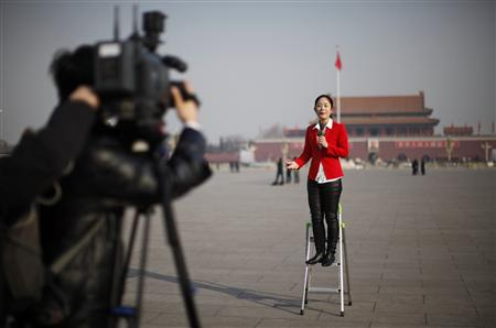 A journalist reports outside the Great Hall of the People at Tiananmen Square during the opening ceremony of the National People's Congress in Beijing
