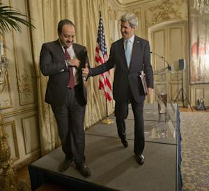 US Secretary of State John Kerry, right, walks off stage with Qatar's Foreign Minister Khalid al-Attiyah, left, following the conclusion of their news conference at the US Ambassador's residence in Paris, France, Sunday, Jan. 12, 2014. Kerry is in Paris to attend a two-day meeting on Syria to rally international support for ending the three-year civil war in Syria. (AP Photo/Pablo Martinez Monsivais, Pool)